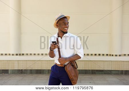 Young African Guy Walking With A Mobile Phone