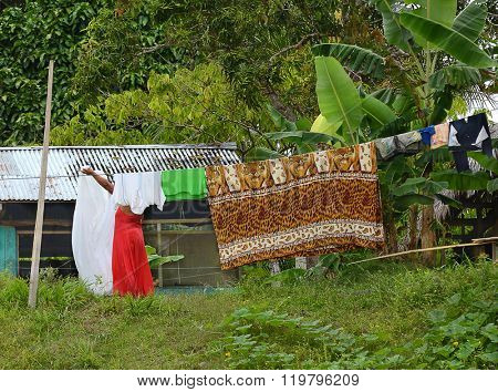 NAUTA, PERU - OCTOBER 14, 2015: Hanging laundry near Nauta. A woman hangs her laundry in front of her home along the banks of the Maranon River.
