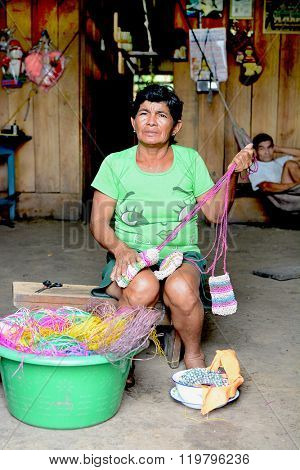 SANTA ANA VILLAGE, PERU - OCTOBER 16, 2015: Woman making handicrafts. Local woman making small bags to sell to tourists in the village market.