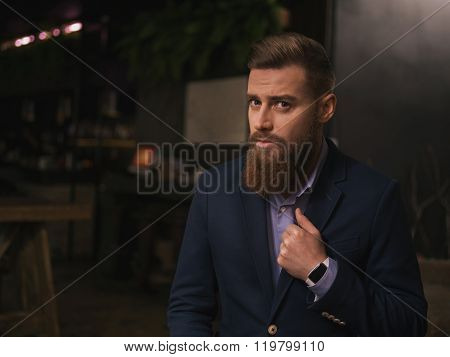 Cheerful young businessman with beard in cafe
