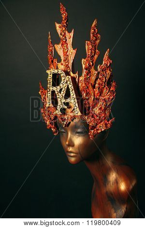 Female Mannequin in red flame headwear on dark background. goddess Ra