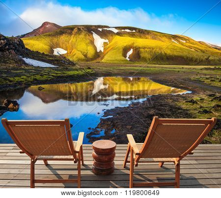 Two wooden chairs and small table stand for tired tourists.  Volcanic summer tundra. Travel to Iceland in July