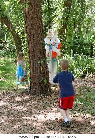 The Easter Bunny playing hide and seek with two young children.