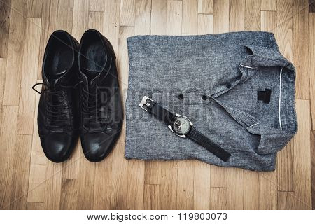 men black leather shoes, gray cotton shirt and wristlet watch on parquet, above view