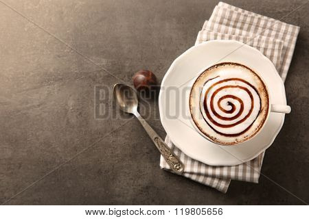 Cup with hot cappuccino with chocolate syrup and candy on grey table