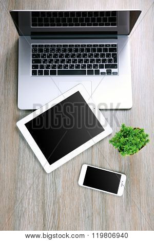 Modern laptop, smart phone and tablet with small green plant on a wooden table