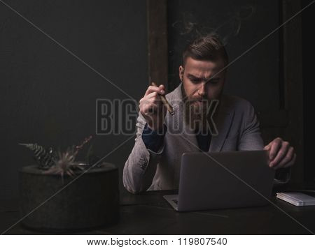 Successful young businessman with an expensive cigarette