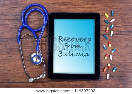 Tablet pc and text Recovery from Bulimia on screen on wooden background