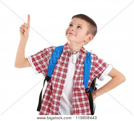Portrait of little boy with back pack pointing finger upwards, isolated on white
