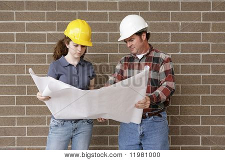 A construction foreman going over blueprints with a female apprentice.