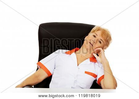 Tired elderly female doctor or nurse sitting behind the desk