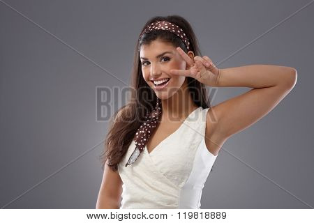 Attractive young woman showing victory sign, smiling happy.