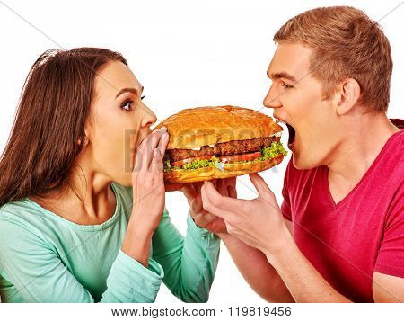 Man and woman biting big hamburgers . Fast food concept. Isolated.