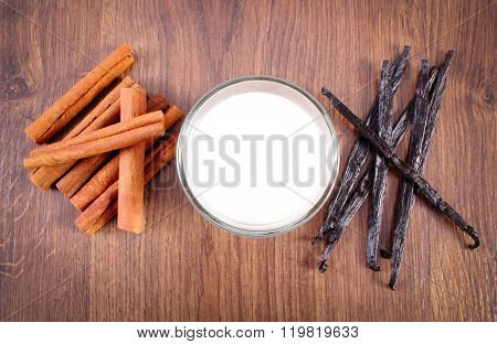 Fragrant Vanilla, Cinnamon Sticks And Glass Of Milk On Wooden Surface