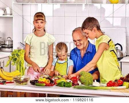 Big family with kids cooking at kitchen. Grandfather and children.