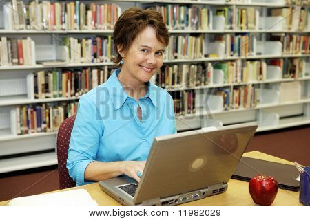 A pretty librarian working on her laptop computer in the school library.