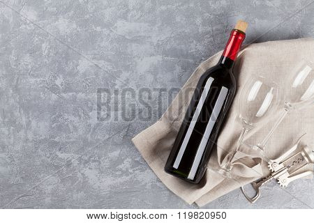 Wine, glasses and corkscrew over gray stone background. Top view with copy space