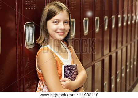 A pretty school girl leaning against her locker.