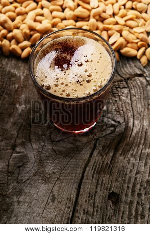 Glass Of Dark Foamy Beer With Snack To Beer Peanuts