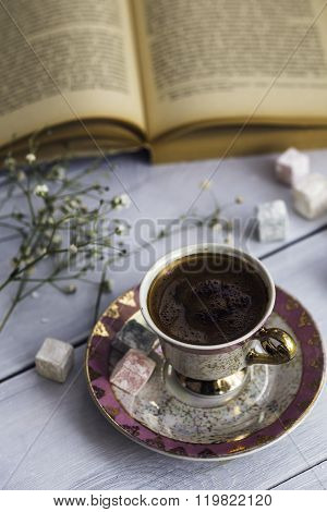 Cup of Turkish coffee with Turkish delights and heart shaped chocolate next to the old book, wooden