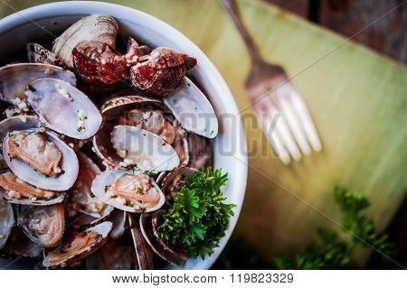 Bowl Of Delicious Fresh Steamer Clams With Garlic And Basil On Rustic Wooden Background