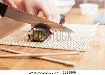 Preparing sushi, cutting. Salmon, avocado, rice on seaweed and chopsticks on wooden table.