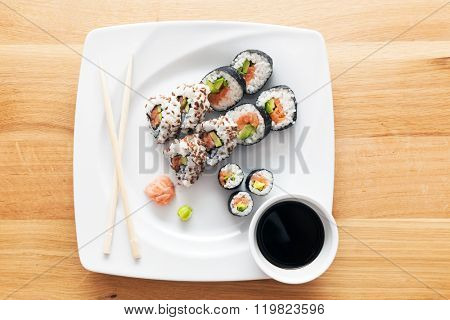 Sushi with salmon, avocado, rice in seaweed and chopsticks served on a plate with wasabi and ginger. Japanese, Asian healthy food. View from the top.