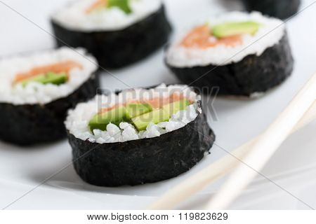 Sushi rolls with salmon, avocado, rice in seaweed and chopsticks on a plate. Japanese, Asian healthy food.