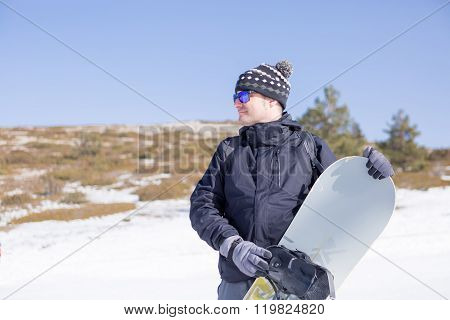Man Holding Snowboard In Snow