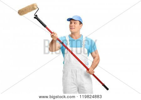 Studio shot of a young male decorator painting with a paint roller isolated on white background