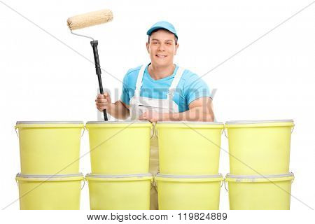 Young male decorator posing behind a stack of color buckets isolated on white background
