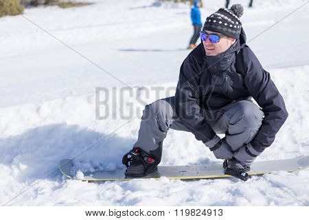 Man Putting On Snowboard