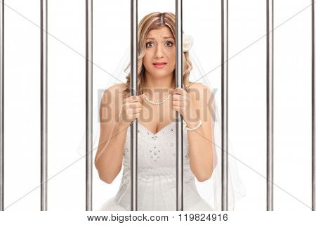 Worried young bride standing behind bars in jail isolated on white background