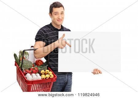 Young man carrying a shopping basket full of groceries and pointing on a blank panel isolated on white background