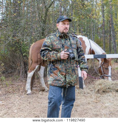 Photographer Man With A Nikon Camera In Camouflage Khaki Jacket Near The Red-white Horse In Reserve