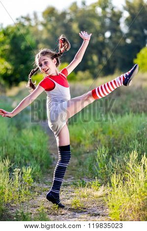 A funny cute outdoor portrait of a little girl presenting Pippi Longstocking and showing out out her tongue.