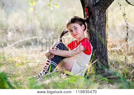 Sad Girl With Pigtails Under The Tree