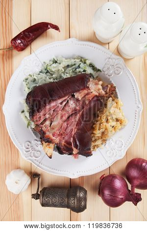 Roasted pork knuckle with potato mash and sour cabbage or sauerkraut