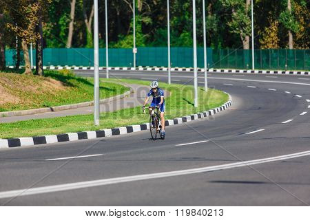 Female cyclist rides a racing bike on road