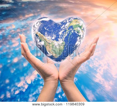 World in heart shape with over women human hands on blurred natural background