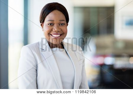 beautiful african saleswoman standing at car dealership