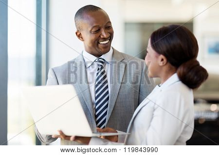 friendly african vehicle dealership principal and saleswoman working on laptop