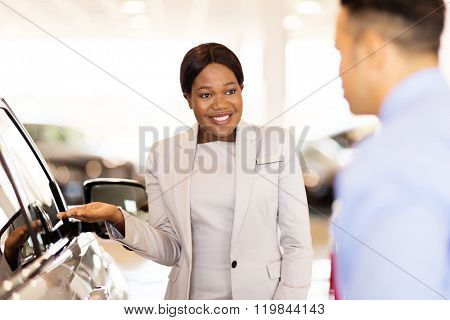 professional african saleswoman selling car to a customer in showroom