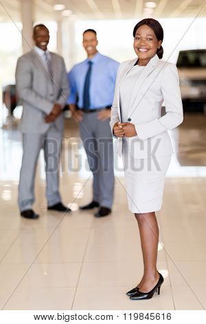 portrait of african car saleswoman with team on background
