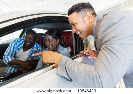 middle aged vehicle salesman showing new car to a happy young couple in showroom