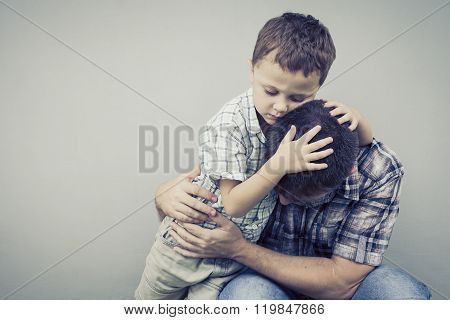 Sad Son Hugging His Dad Near Wall