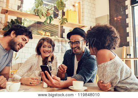 Friends In A Cafe Looking At The Photos On Mobile Phone