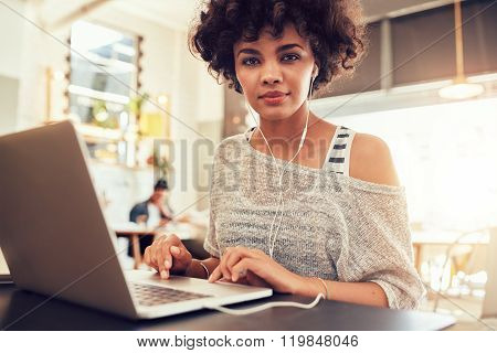 African Woman Sitting In Coffee Shop With A Laptop