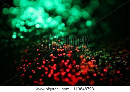 Macro detail of optical fibers transmitting data in red and green
