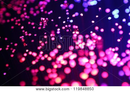 Purple colored optical fibers on black background